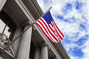 american flag on stone granite government building